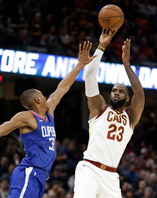 . Cleveland Cavaliers\' LeBron James, right, shoots over Los Angeles Clippers\' Wesley Johnson during the first half of an NBA basketball game, Friday, Nov. 17, 2017, in Cleveland. The Cavaliers won 118-113 in overtime. (AP Photo/Tony Dejak)