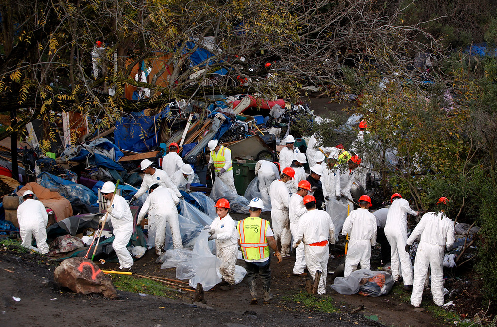 . An army of workers descends on The Jungle homeless camp as it is closed by the city Thursday morning, Dec. 4, 2014, in San Jose, Calif. (Karl Mondon/Bay Area News Group)