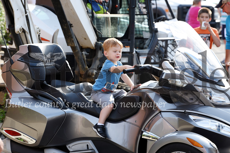 Harold Aughton/Butler Eagle: Austin Stahurski, 2, of Mars touches the buttons on a motorcycle during the touch-a-truck event in Evans City, Wednesday, July 24.