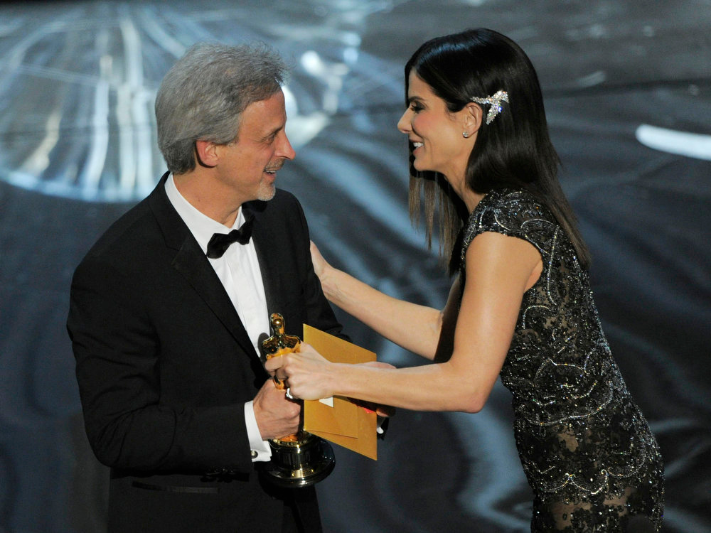 ". Actress Sandra Bullock, right, presents the award for best film editing to William Goldenberg for ""Argo\"" during the Oscars at the Dolby Theatre on Sunday Feb. 24, 2013, in Los Angeles.  (Photo by Chris Pizzello/Invision/AP)"