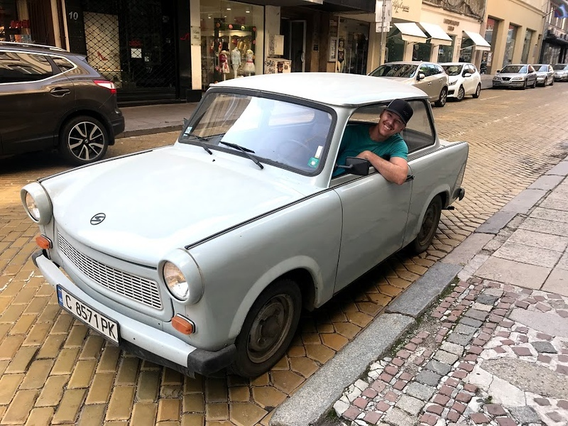 man hanging his elbow out of trabant car