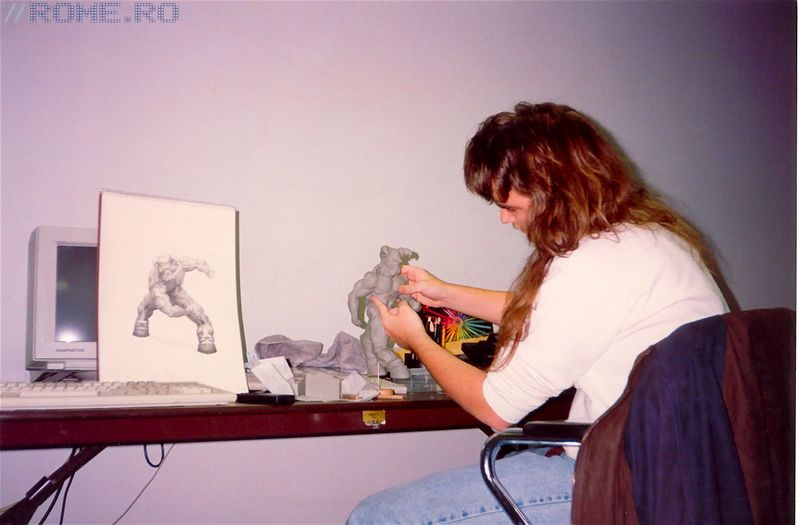 This picture was taken during DOOM development in 1993. Adrian's in his room (which he shared with Kevin Cloud) and you can see here that he was modeling the Baron of Hell out of clay himself, based on his own sketch of the Baron.  Also, this was the very first clay model that was made for DOOM.  At this stage, he wasn't called the Baron of Hell, but rather, a Bruiser Brother (since there were two of them at the end of the first episode of DOOM.
