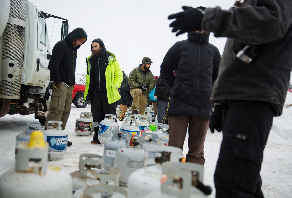 . People wait to have their propane tanks filled at the Oceti Sakowin camp where people have gathered to protest the Dakota Access oil pipeline in Cannon Ball, N.D., Thursday, Dec. 1, 2016. (AP Photo/David Goldman)