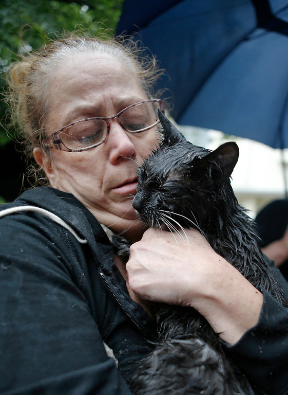 . Cindy Piscopo cuddles her very wet cat Zack after firefighter Lou Femia spotted the cat while battling a blaze in a series of three townhouses, including the one where Piscopo lived, in the Staten Island borough of New York, Thursday, June 5, 2014.  (AP Photo/Kathy Willens)