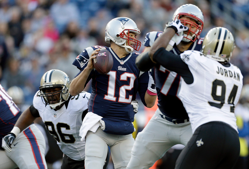 . New England Patriots quarterback Tom Brady (12) looks for a receiver as New Orleans Saints defensive tackle Tom Johnson (96) and defensive end Cameron Jordan (94) pursue in the first quarter of an NFL football game Sunday, Oct.13, 2013, in Foxborough, Mass. (AP Photo/Steven Senne)