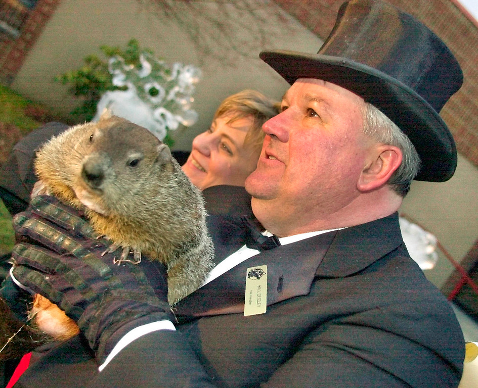 . Punxsutawney Phil is held by handler Bill Deeley as he poses Friday, Feb. 1, 2002, with Ruth Golladay of Moneta, Va., who traveled to Punsutawney to celebrate her Feb. 2 birthday in Punsutawney, Pa. Mr. Deeley and other members of the Punxsutawney Groundhog Club will make the 116th trek to Gobbler\'s Knob Saturday to hear Phil\'s prediction on a possible early end to winter, and on the outcome of the Super Bowl.(AP Photo/Gene J. Puskar)