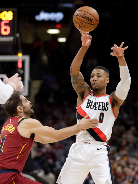 . Portland Trail Blazers\' Damian Lillard (0) passes over Cleveland Cavaliers\' Jose Calderon (81), from Spain, in the first half of an NBA basketball game, Tuesday, Jan. 2, 2018, in Cleveland. (AP Photo/Tony Dejak)
