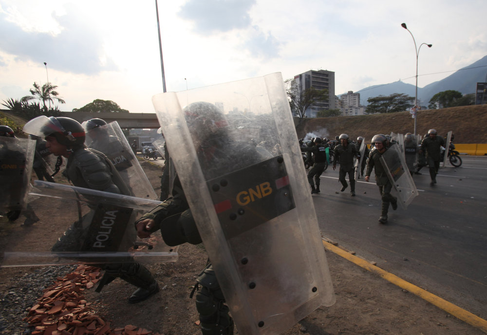 . Riot police charges towards demonstrators as opposition supporters and students block a highway in the Altamira neighborhood in Caracas, Venezuela, Monday, April 15, 2013. National Guard troops fired tear gas and plastic bullets to disperse demonstrators protesting the official results in Venezuela\'s disputed presidential election.(AP Photo/Fernando Llano)
