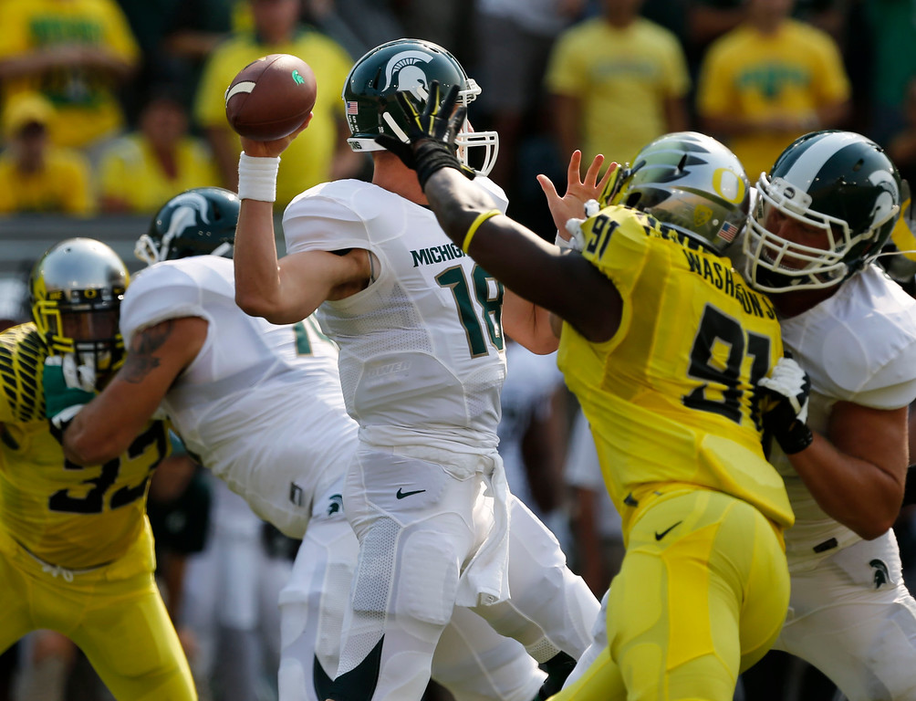 . Michigan State quarterback Connor Cook, left, passes down field under pressure from Oregon\'s Tony Washington during the first quarter of their college football game in Eugene, Oregon, Saturday Sept. 6, 2014. (AP Photo/Chris Pietsch)