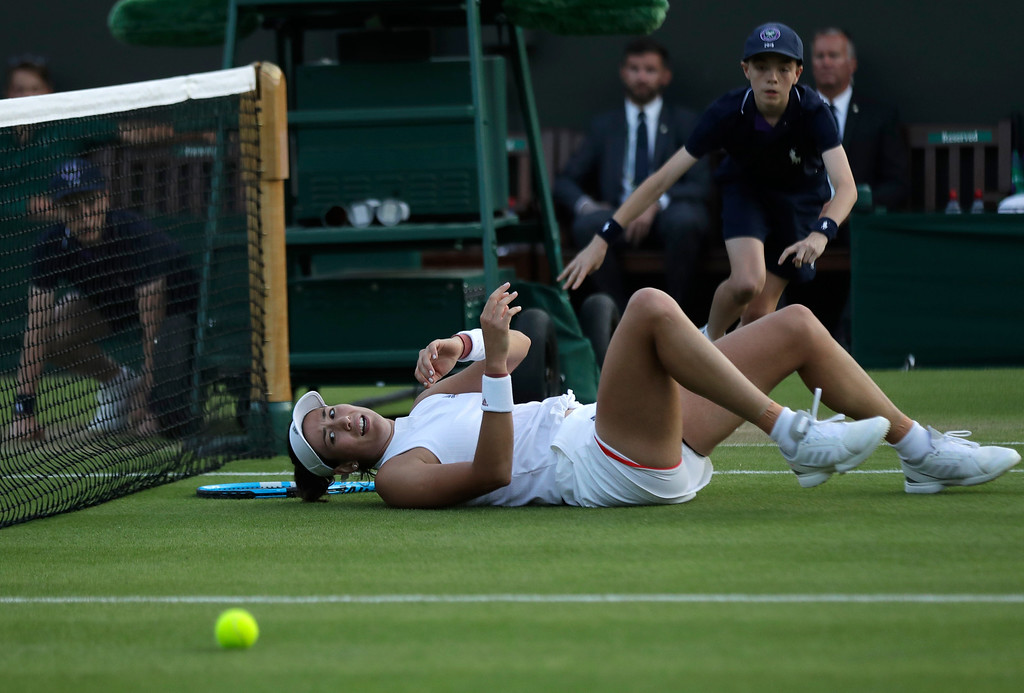 . Spain\'s Garbine Muguruza falls trying to return the ball to Alison Van Uytvanck of Belgium, during their women\'s singles match, on the fourth day at the Wimbledon Tennis Championships in London, Thursday July 5, 2018. (AP Photo/Ben Curtis)
