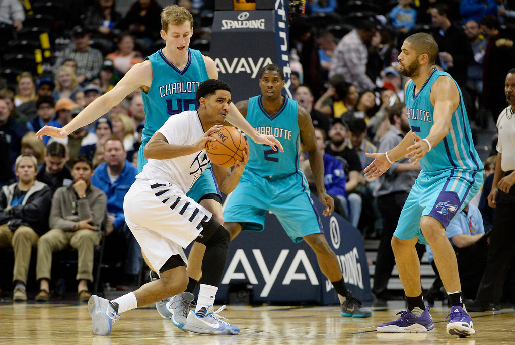 . Gary Harris (14) of the Denver Nuggets controls the ball as he is defended by Cody Zeller (40) of the Charlotte Hornets, Marvin Williams (2) and Nicolas Batum (5) during the third quarter of the Nuggets\' 95-92 win. The Denver Nuggets hosted the Charlotte Hornets at the Pepsi Center on Sunday, January 10, 2016. (Photo by AAron Ontiveroz/The Denver Post)