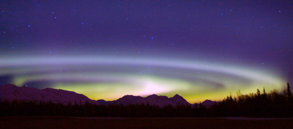 Description of . In this Feb. 29, 2008 file photo, an Aurora Borealis spins above the Talkeetna Range and a hay field on Farm Loop Road near Palmer, Alaska. (AP Photo/Bob Martinson/FILE)