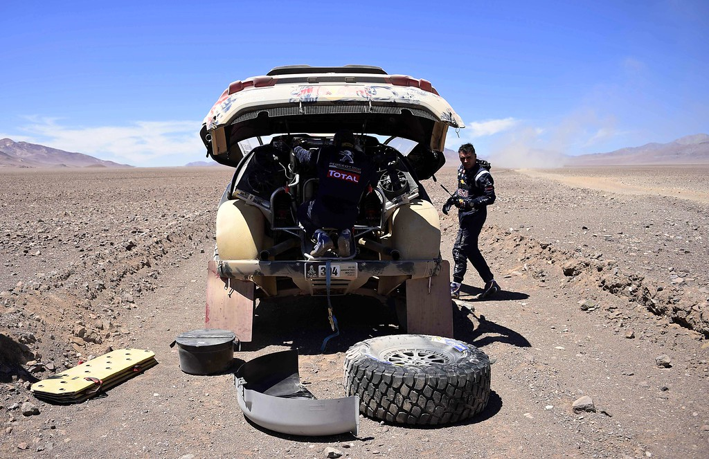 . Peugeot\'s driver Carlos Sainz (L) of Spain and co-driver Lucas Cruz (R) check their car after stopping due to technical problems during the Stage 4 of the Dakar 2015 between Chilecito, in Argentina and Copiapo, Chile, on January 7, 2015. FRANCK FIFE/AFP/Getty Images