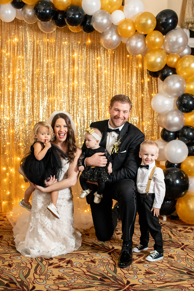 Photo booth backdrop for Lizzie and Craig's New Year's Eve wedding at New Year's Eve wedding Norbeck Country Club.  The New Year's Eve photo booth included gold sequin pipe and drape and black, white and gold balloons.