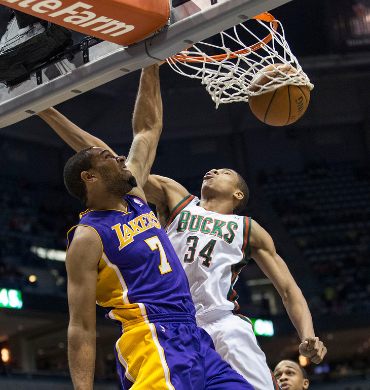 . Milwaukee Bucks\' Giannis Antetokounmpo can not stop Los Angeles Lakers\' Xavier Henry from dunking the ball during the first half of an NBA basketball game Thursday, March 27, 2014, in Milwaukee. (AP Photo/Tom Lynn)
