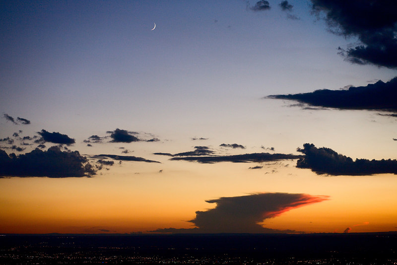 A distant thunderhead and crescent moon