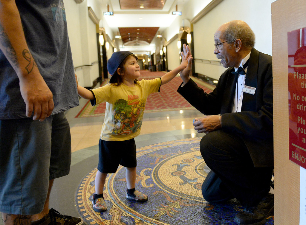 . Al Harris, floor manager of the Krikorian Premier Theatre, greets Marley Moreno, 3, of Redlands and his father Felipe, before the start of their movie, Thursday, in Redlands,Ca., Feb. 13, 2014. Harris has become a local icon collecting tickets and giving high fives to moviegoers since being hired by Krikorian in 1992.  (John Valenzuela/Photographer)