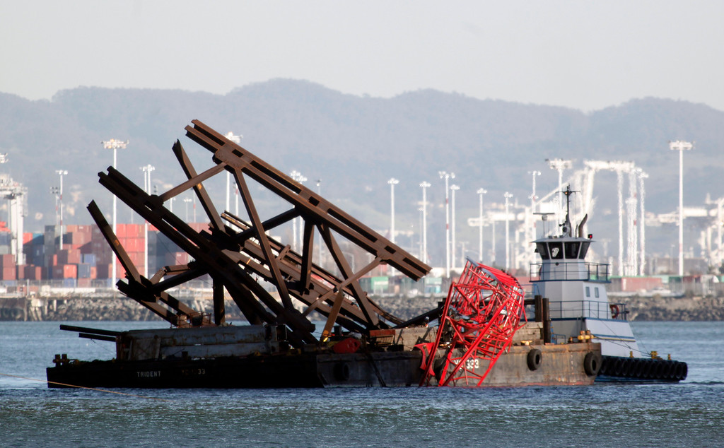 . A tug pushes a barge carrying a piece falsework and a section of a toppled crane away from the new Bay Bridge project after an accident near Treasure Island onThursday, Feb. 21, 2013 in San Francisco. (Karl Mondon/Staff)