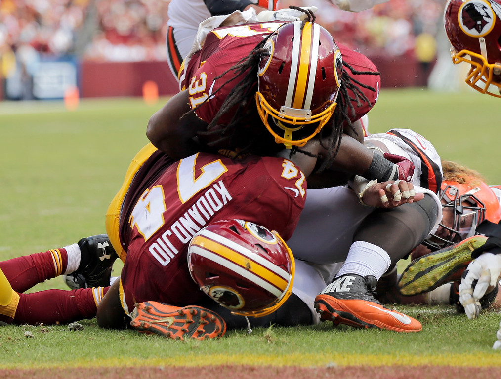 . Washington Redskins running back Matt Jones (31) goes over offensive guard Arie Kouandjio (74) and Cleveland Browns nose tackle Danny Shelton for a touchdown during the second half of an NFL football game Sunday, Oct. 2, 2016, in Landover, Md. (AP Photo/Mark Tenally)