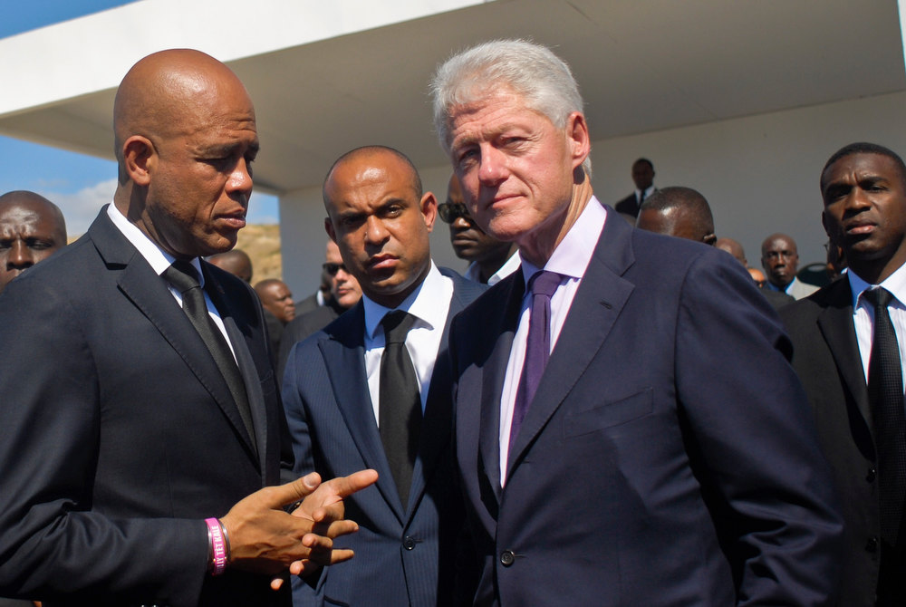 . Haiti\'s President Michel Martelly (L), former U.S. President Bill Clinton (2nd R) and Haiti\'s Prime Minister Laurent Lamothe (C) attend a memorial service remembering the lives lost in the January 2010 earthquake at the mass burial site at Morne St. Christophe January 12, 2013. Clinton flew to Haiti on Saturday to join the country\'s president, Michel Martelly, at an official commemoration of the third anniversary of the earthquake that decimated the capital and killed more than 250,000 people. REUTERS/Swoan Parker