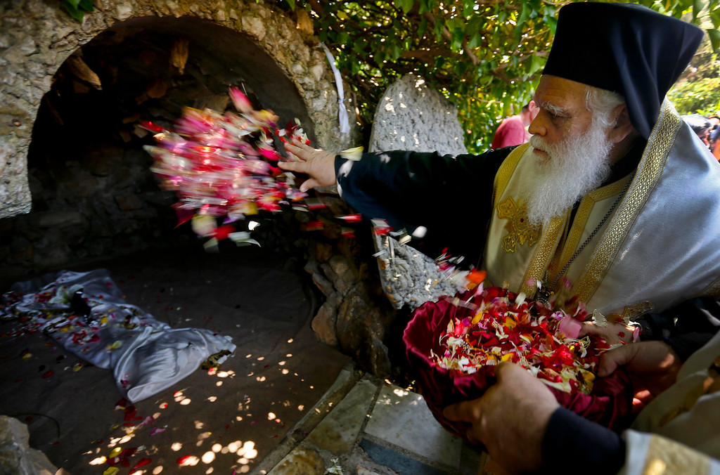 . Metropolitan Ioannis of Thermopylae throws flowers inside a crypt with a figure of a crucified Jesus Christ during a mass on Good Friday at Penteli monastery north of Athens May 3, 2013. Orthodox Christians around the world celebrate Easter on Sunday. REUTERS/Yannis Behrakis