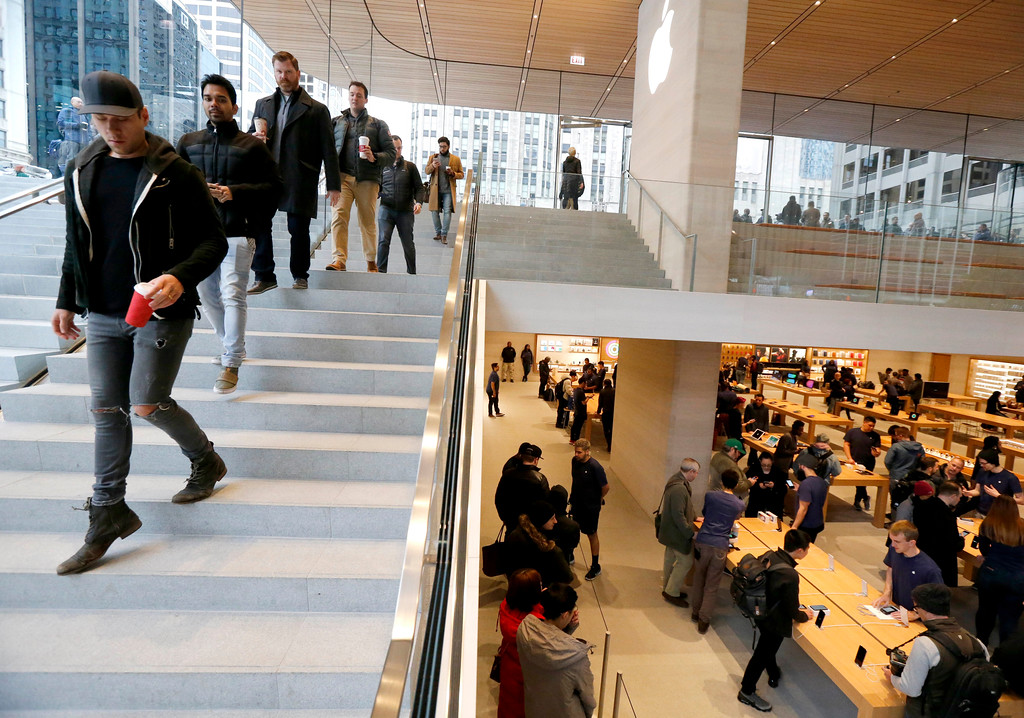 . Consumers descend into the new Apple Michigan Avenue store along the Chicago River to buy the Apple iPhone X Friday, Nov. 3, 2017, in Chicago. (AP Photo/Charles Rex Arbogast)