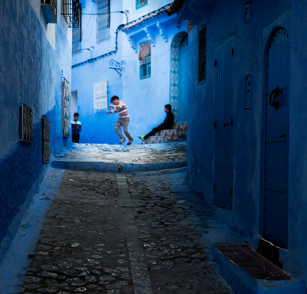 Children playing in the northern blue city of Chefchaouen.  Chefchaouen, Morocco, 2018