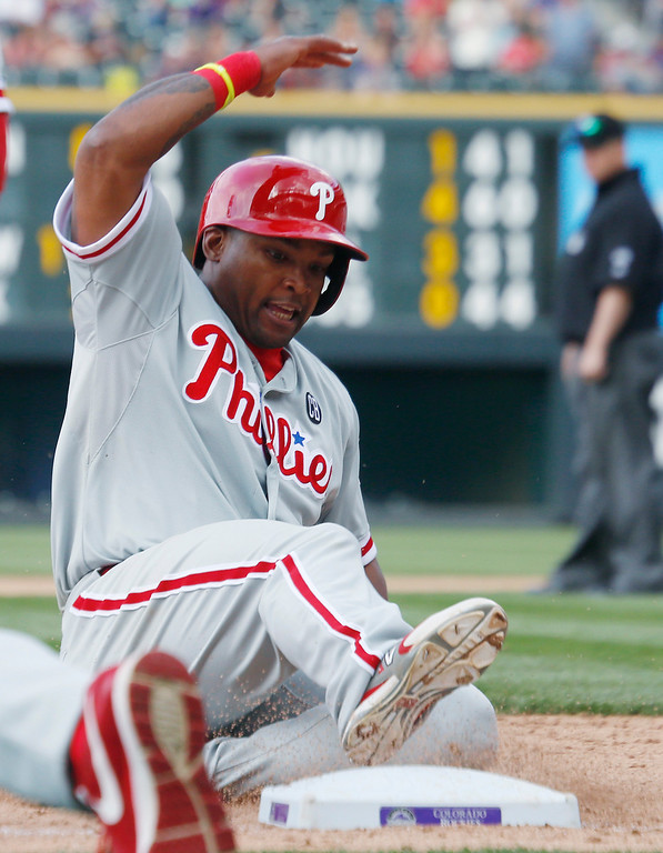 . Philadelphia Phillies\' Marlon Byrd slides safely into third base as he advances on a sacrifice fly hit by Domonic Brown against the Colorado Rockies in the ninth inning of the Phillies\' 10-9 victory in a baseball game in Denver on Sunday, April 20, 2014. (AP Photo/David Zalubowski)