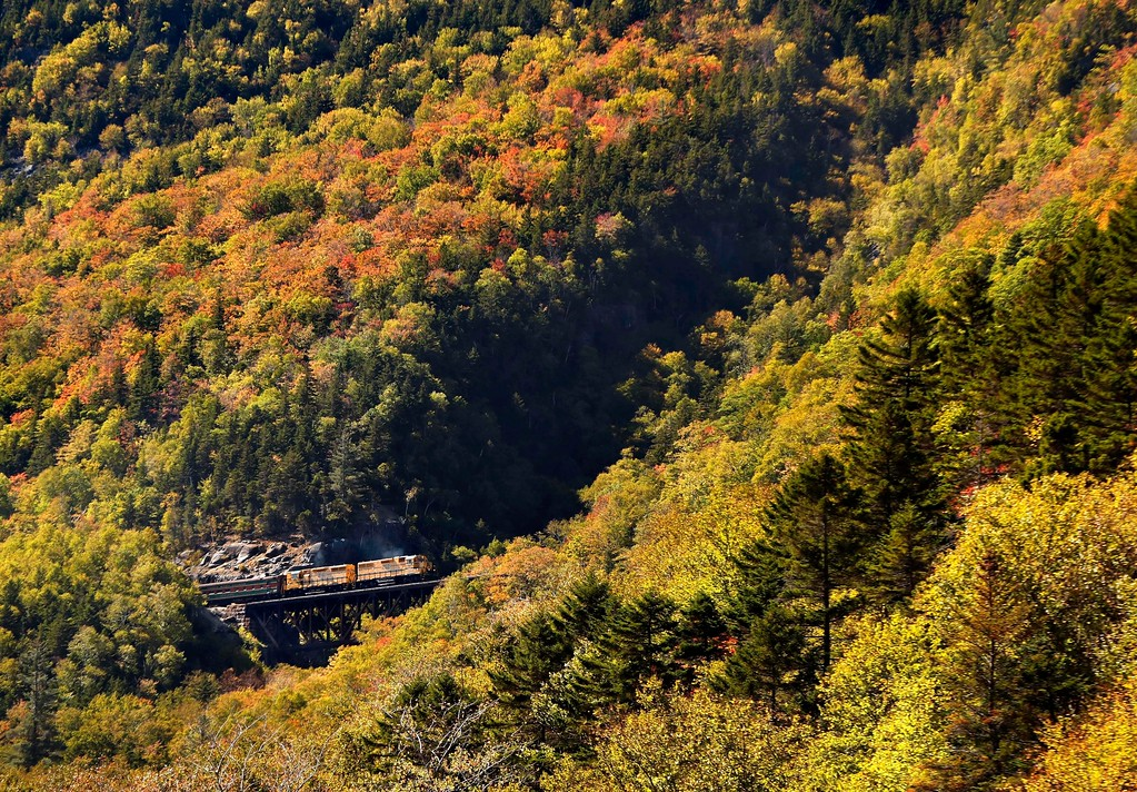 . The Conway Scenic Railroad crosses a trestle as it takes passengers on a fall foliage excursion through Crawford Notch, N.H., Sunday, Oct. 1, 2017. The train passes many panoramic vistas on its route through the White Mountain National Forest from North Conway to Crawford station. (AP Photo/Robert F. Bukaty)