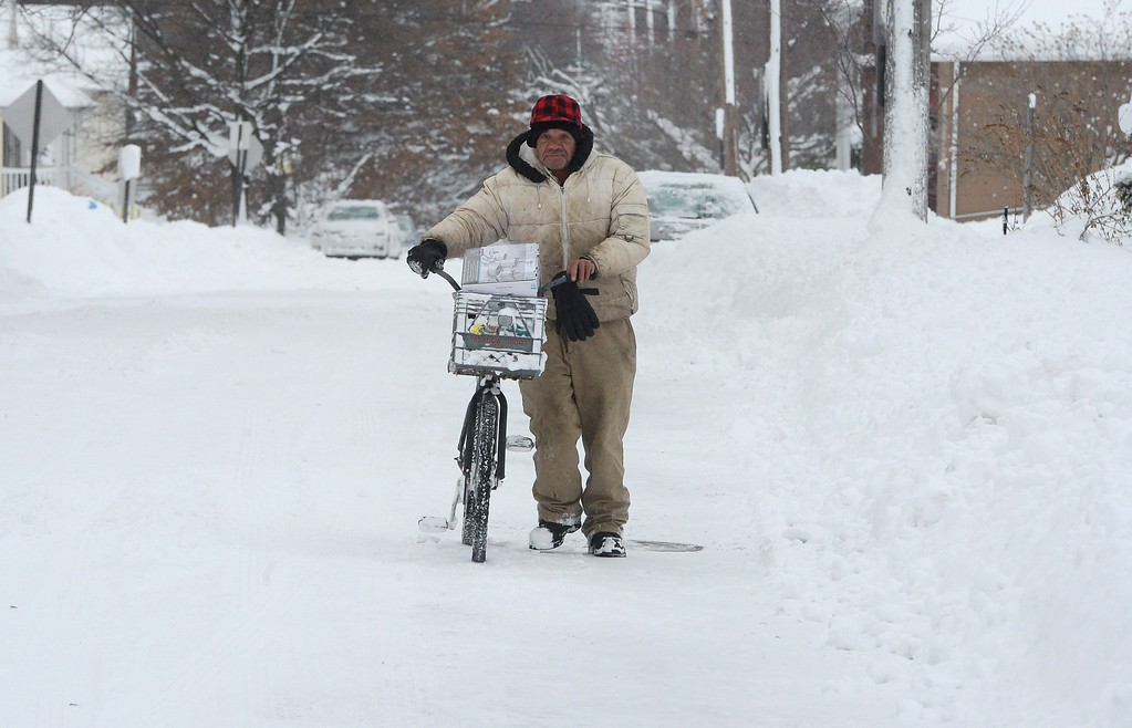 . Logan Rogers pushes his bike along East Third Street in Erie, Pa., Wednesday, Dec. 27, 2017. Freezing temperatures and below-zero wind chills socked much of the northern United States on Wednesday, and the snow-hardened city of Erie, dug out from a record snowfall.  (Jack Hanrahan/Erie Times-News via AP)