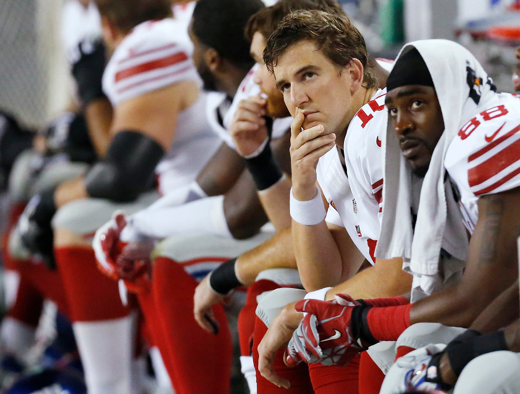 . New York Giants quarterback Eli Manning (10) and wide receiver Hakeem Nicks (88) watch from the bench in the first half of an NFL football game against the Chicago Bears, Thursday, Oct. 10, 2013, in Chicago. (AP Photo/Charles Rex Arbogast)