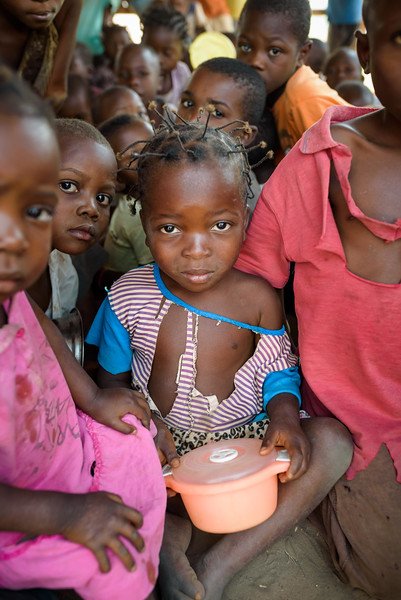 Children wait for the supplemental feeding to begin, at the Child Friendly Space that Marie Ngalula, 14, and her siblings attend.  Marie lives with her father, Alexandre Tshimanga, her mother, Ntumba Kalombo Antoinette and her brothers and sisters: 1-Kena Tshimanga, 12 2-Kankonde Moise, 10 3-Munamba Angel, 8 4-Musungayi Andre, 6 5-Mubuyi Tshimanga, 4  Marie lives in a small village outside of Kananga, Democratic Republic of Congo, DRC, called Tubuluku, which means antelopes (plural). Her house is a two-room hut with a thatched roof.  Handful of wooden chairs are the only furniture. She lives here with an extended family of 13.  Home Life Marie is a bright girl but there is a sadness in her eyes. Marie's mother is in the nearby health clinic with a staph infection that has caused a huge abscess on her right side. It has become very serious. As a result, Marie has assumed many of the household duties.  She's forced, at 14, to assume the duties of an adult. Besides cooking for her brothers and sisters, she sweeps up the husks from palm nuts she crushes. She saves the husks to use as kindling for the fire. Marie and her siblings all sleep together in one room, huddled together for warmth and cover by an old and torn mosquito net.  Hunger Marie's family is desperately hungry in the days we visit them. Because her mother is sick and his father spends his days tending to her in the clinic, there is no money for food. Because there isn't any cassava flour and cornmeal to make fufu, a bread-like dish that's a Congolese staple, Marie and her siblings pick potato leaves from the garden. Marie sharpens a knife on a rock and uses it to chop the leaves into small pieces. She holds a bunch tightly in her left hand and runs the knife through them.  Her cousin, also named Marie Ngalula, pulls some wood from a pile and arranges it between three rocks that will hold the pot. She yanks some thatch from the roof and uses it for kindling. Because they also have no oil or salt, the recipe