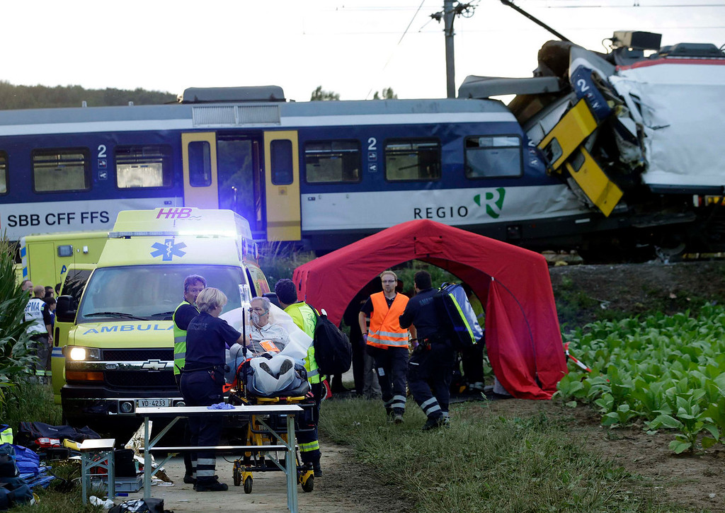 . Rescue workers transport a wounded person on a stretcher after a head on collision between two trains near Granges-pres-Marnand, near Payerne in western Switzerland, July 29, 2013. The two trains collided at Granges-pres-Marnand in the Swiss canton of Vaud on Monday evening, injuring about 40 people, four seriously, Swiss news agency ATS reported. There was no immediate report of any deaths in the crash.  REUTERS/Denis Balibouse