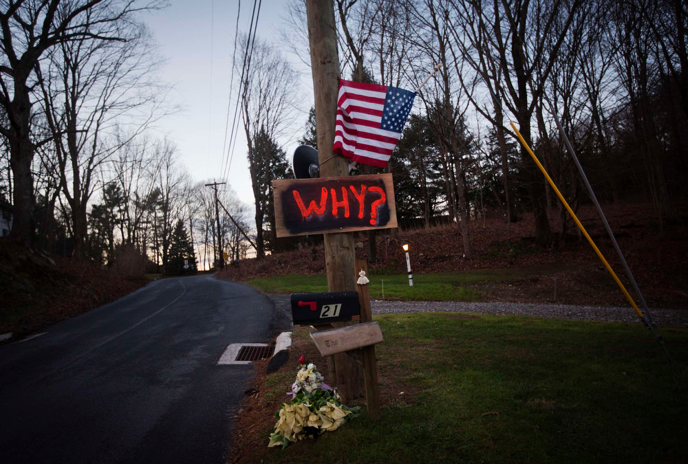 . A sign, flag and flowers are seen outside a home honoring victims who died in the December 14 shootings at Sandy Hook Elementary School, in Newtown, Connecticut December 19, 2012. Six more victims of the Newtown school shooting will be honored at funerals and remembrances on Wednesday, including the school principal who was killed with 20 of her students and five other staff members at the Sandy Hook Elementary School.   REUTERS/Shannon Stapleton
