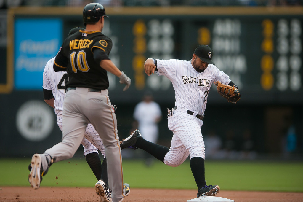 . Wilin Rosario #20 of the Colorado Rockies runs to first base with the ball as Jordy Mercer #10 of the Pittsburgh Pirates grounds out in the first inning of a game at Coors Field on July 26, 2014 in Denver, Colorado. (Photo by Dustin Bradford/Getty Images)