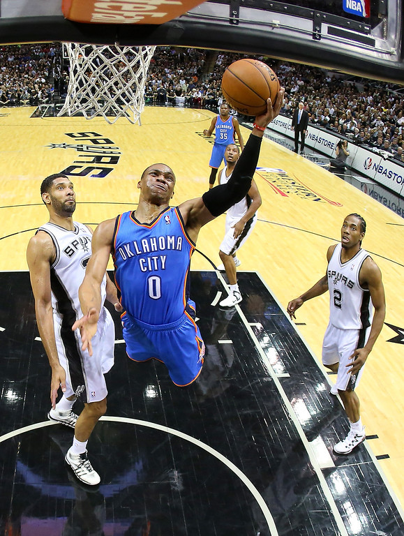 . Russell Westbrook #0 of the Oklahoma City Thunder goes up for a shot in front of Tim Duncan #21 of the San Antonio Spurs in the first half in Game Two of the Western Conference Finals during the 2014 NBA Playoffs at AT&T Center on May 21, 2014 in San Antonio, Texas.  (Photo by Ronald Martinez/Getty Images)