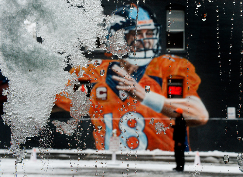 . Broncos fan James Buckmaster checks out the work of street muralist Gamma Acosta portrait of Peyton Manning in spray paint, seen through ice and snow on a car window, after Denver was hit with a few inches of new snow overnight, January, 31 2014. A smaller storm will move back into the area later today. (Photo by RJ Sangosti/The Denver Post)