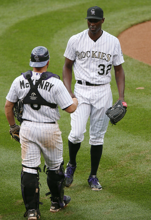 . Colorado Rockies catcher Michael McKenry, front, congratulates relief pitcher LaTroy Hawkins after he retired the Washington Nationals in the ninth inning of the Rockies\' 6-4 victory in a baseball game in Denver on Wednesday, July 23, 2014. (AP Photo)