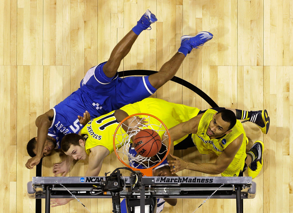. Michigan\'s Jon Horford, right, follows up a shot as players lay on the court during the first half of an NCAA Midwest Regional final college basketball tournament game against Kentucky Sunday, March 30, 2014, in Indianapolis. (AP Photo/Michael Conroy)