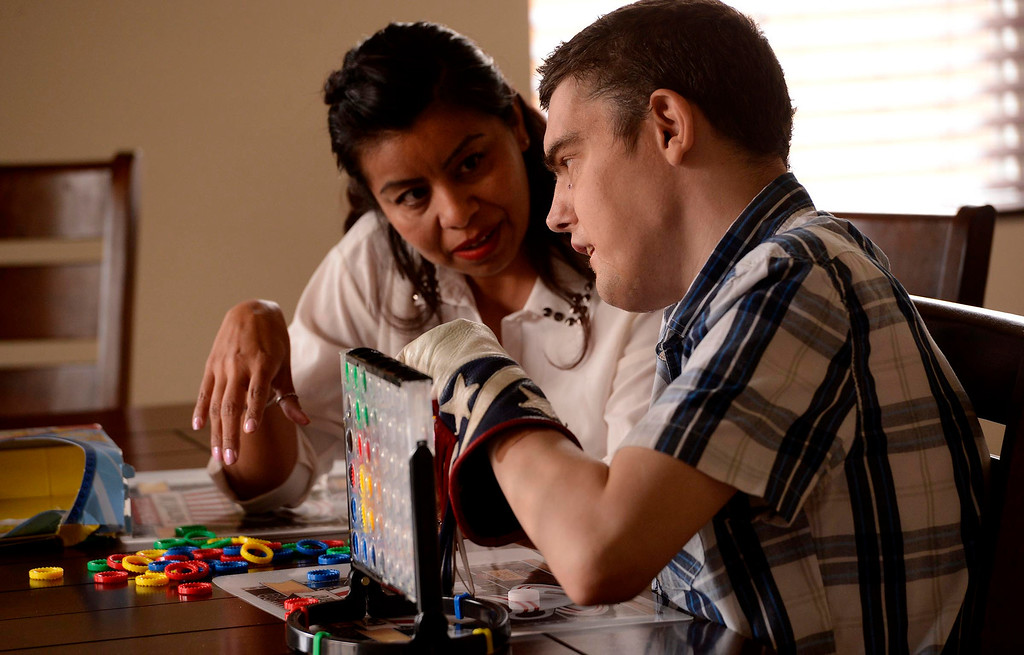 . Carina Rodriguez, left, spends time with patient David Stein as he plays a game at a community home in San Bernardino July 11, 2013.  Stein, 36, is one of many developmentally disabled California residents who are transitioning from state institutions into community homes as the state closes its developmental centers. Stein moved into the 24-hour care group home about a year ago from Lanterman Developmental Center in Pomona and is doing well.  GABRIEL LUIS ACOSTA/STAFF PHOTOGRAPHER.