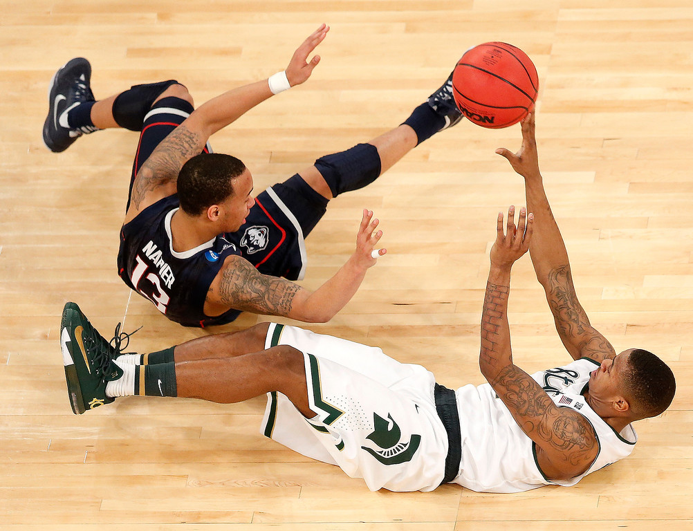 . Connecticut guard Shabazz Napier, left, and Michigan State guard Keith Appling fall while competing for a loose ball during the first half in a regional semifinal at the NCAA college basketball tournament on Sunday, March 30, 2014, in New York. (AP Photo/Julio Cortez)