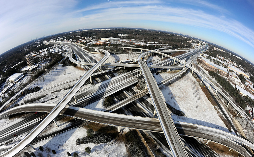 """. In this photo taken with a fisheye lens over the city\'s perimeter highway known as \""""Spaghetti Junction,\"""" the ice-covered interstate system shows the remnants of a winter snow storm that slammed the city with over 2 inches of snow that turned highways into parking lots when motorists abandoned their vehicles creating massive traffic jams lasting through, Wednesday, Jan. 29, 2014, in Atlanta. While such amounts of accumulation barely quality as a storm in the north, it was enough to paralyze the Deep South. (AP Photo/David Tulis)"""