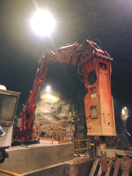 NPK B550 pedestal boom system with GH7 hydraulic hammer-breaking bridged rock abover a grizzly style crusher in a mine (6).jpg