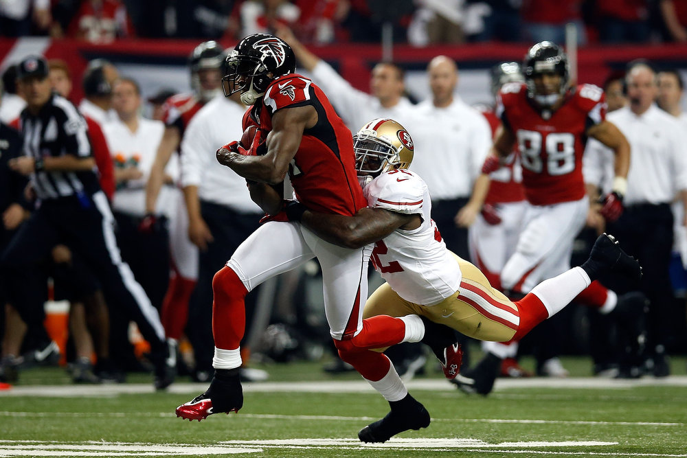 Description of . Wide receiver Julio Jones #11 of the Atlanta Falcons runs after a catch as inside linebacker Patrick Willis #52 of the San Francisco 49ers attempts to tackle Jones in the first quarter in the NFC Championship game at the Georgia Dome on January 20, 2013 in Atlanta, Georgia.  (Photo by Chris Graythen/Getty Images)