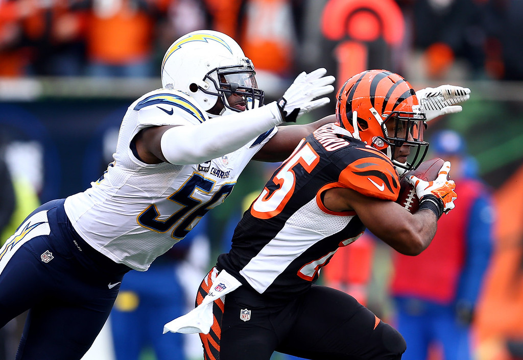 . Running back Gio Bernard #25 of the Cincinnati Bengals carries the ball as outside linebacker Tourek Williams #58 of the San Diego Chargers defends during a Wild Card Playoff game at Paul Brown Stadium on January 5, 2014 in Cincinnati, Ohio.  (Photo by Andy Lyons/Getty Images)