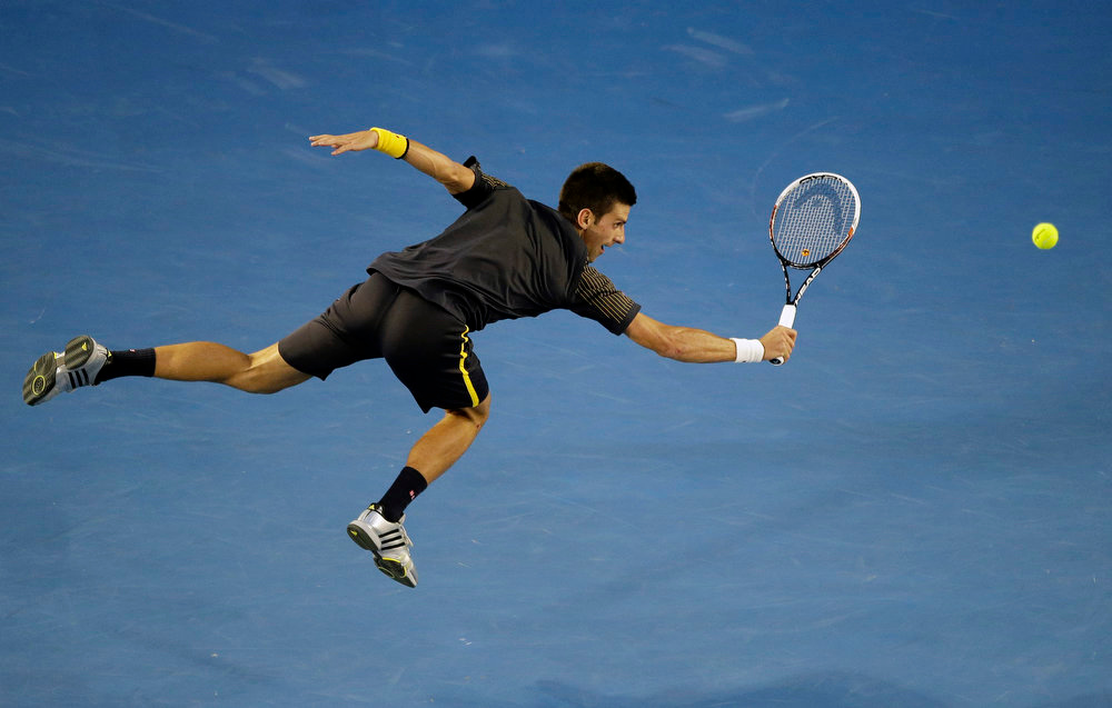 Description of . Serbia\'s Novak Djokovic makes a backhand return to Britain\'s Andy Murray during the men\'s final at the Australian Open tennis championship in Melbourne, Australia, Sunday, Jan. 27, 2013. (AP Photo/Rob Griffith)