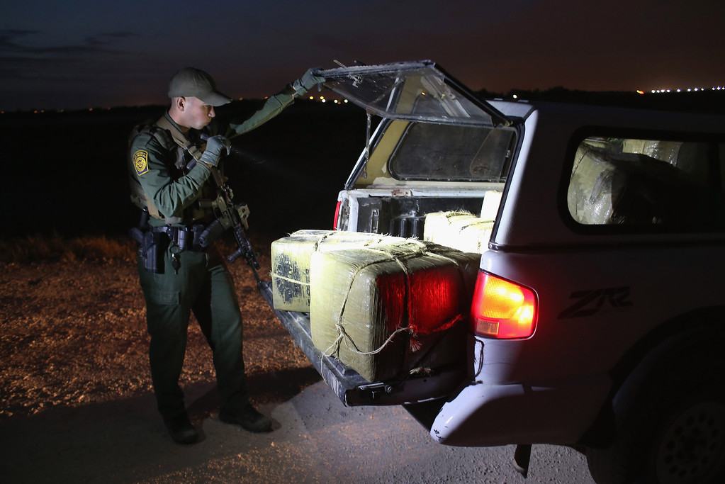 . HIDALGO, TX - APRIL 10:  A U.S. Border Patrol Agent inspects a load of marijuana seized from drug smugglers near the U.S.-Mexico border on April 10, 2013 in Hidalgo, Texas. The agents, guided by helicopter surveillance from the U.S. Office of Air and Marine, waited more than four hours in hiding before seizing more than 900 pounds of the drug. The smugglers ran and escaped by swimming back across the Rio Grande River into Mexico. Border Patrol agents say they have also seen an additional surge in immigrant traffic since immigration reform negotiations began this year in Washington D.C. Proposed refoms could provide a path to citizenship for many of the estimated 11 million undocumented workers living in the United States.  (Photo by John Moore/Getty Images)