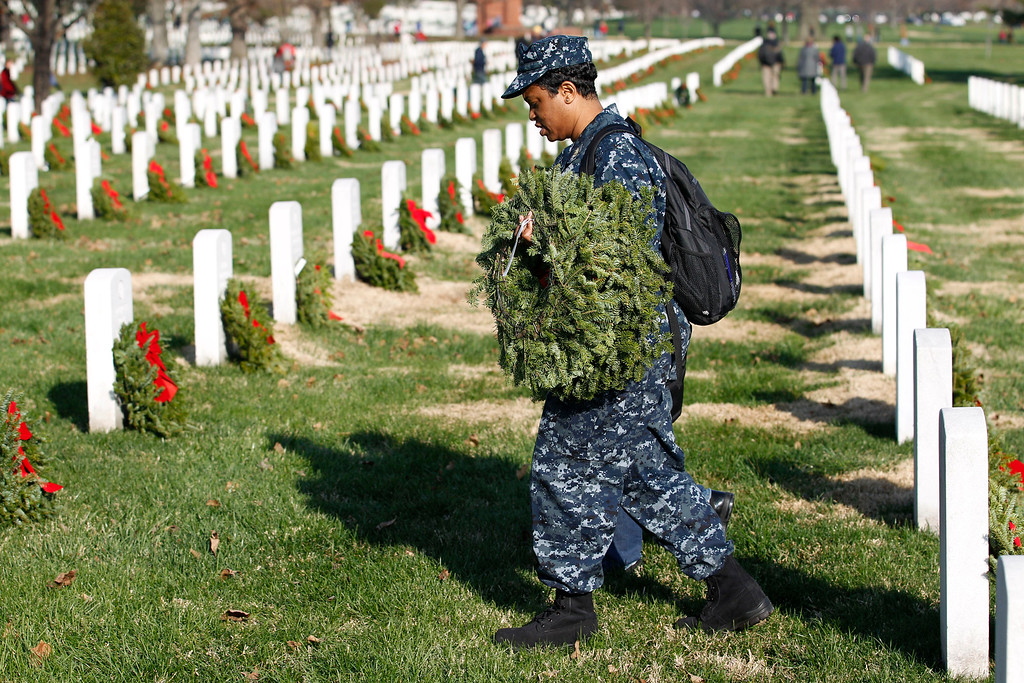 . Navy HMC Shawntell Williams help to place holiday wreaths at the graves of fallen soldiers during Wreaths Across America Day at Arlington National Cemetery on Saturday Dec. 10, 2011.  (AP Photo/Jose Luis Magana)