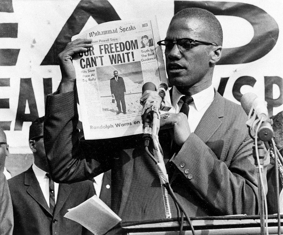 . Black Muslim leader Malcolm X holds up a paper for the crowd to see during a Black Muslim rally in New York City on Aug. 6, 1963.  (AP Photo)