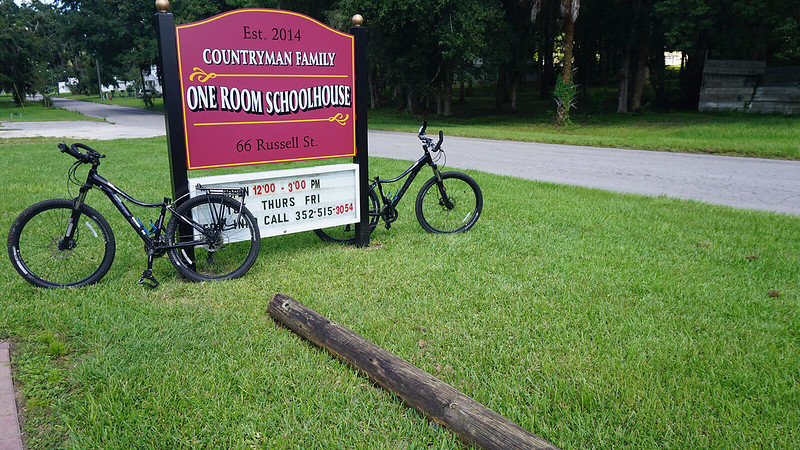 Two bikes leaning against historic schoolhouse sign